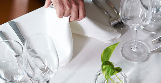 A napkin being place in a table setting